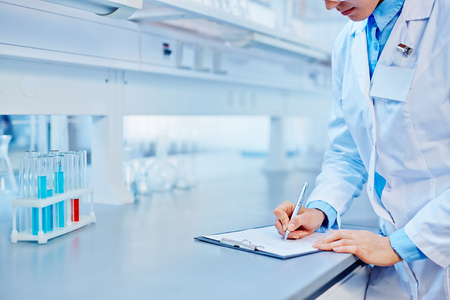 Female lab worker making notes Stock Photo
