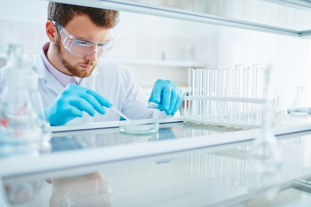 Male chemist carrying out scientific experiment in laboratory Фото со стока