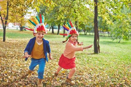 headdresses: Cute girl and boy in Indian headdresses running in autumn park