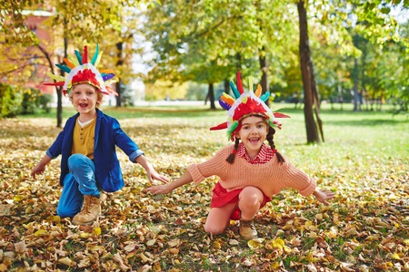 headdresses: Cheerful girl and boy in Indian headdresses playing outdoors Stock Photo