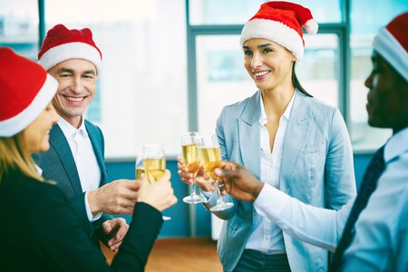 office party: Happy office workers in Santa caps toasting at Christmas party Stock Photo