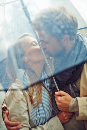 amorous woman: Amorous man and woman kissing under umbrella