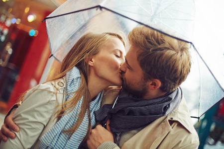 Amorous young couple kissing under umbrella Imagens
