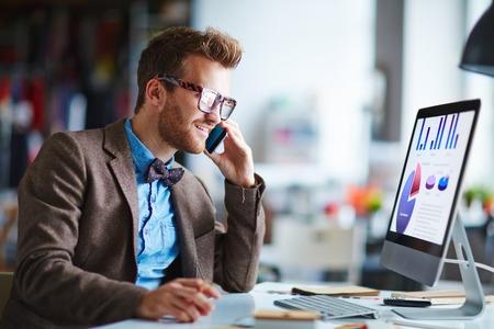 empleados trabajando: Empleado ocupado hablando por teléfono mientras mira la pantalla de la computadora