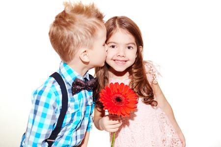 ni�as peque�as: Ni�o peque�o besa a la chica linda con gerbera rojo