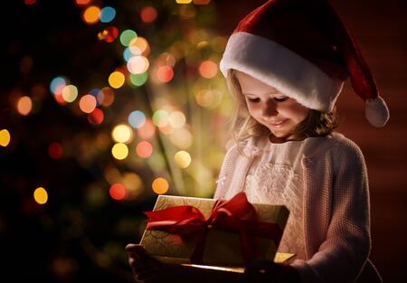 christmas gift box: Cute child in Santa cap opening box with Christmas gift Stock Photo
