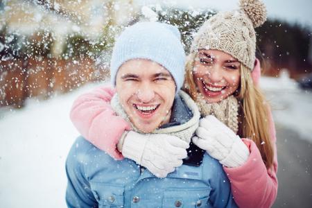 Young guy and girl in winterwear enjoying snowfall Archivio Fotografico