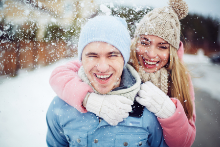 human relationships: Young guy and girl in winterwear enjoying snowfall Stock Photo