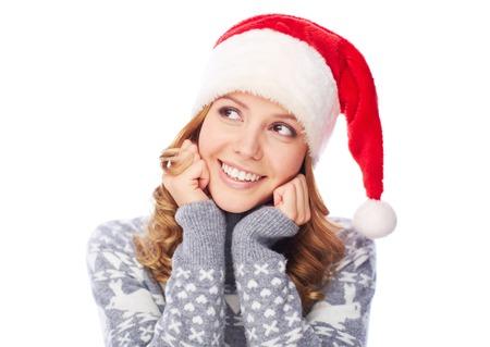 christmastide: Happy girl in Santa cap looking sideways Stock Photo