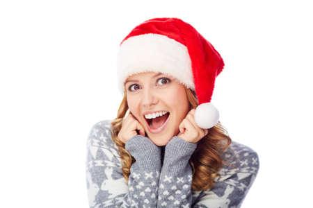 christmastide: Surprised girl in Santa cap looking at camera