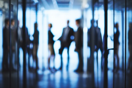 modern business: Silhouettes of business partners interacting in corridor of business center Stock Photo
