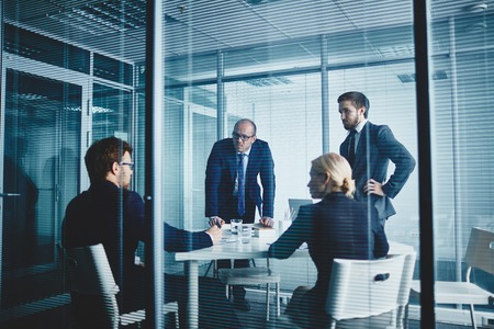 corporate consulting: Several colleagues gathered in office for discussing plans