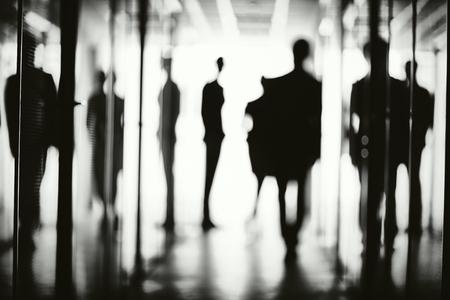silueta hombre: Siluetas de varios trabajadores de oficina en el pasillo del centro de negocios Foto de archivo