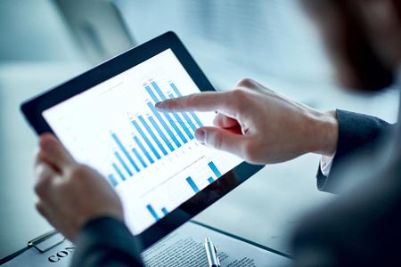 財務データとグラフを指してビジネスマン