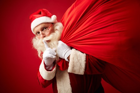 quiet: Santa showing shh gesture while carrying sack with xmas gifts