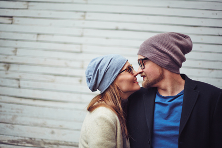 touching noses: Romantic dates in stylish casualwear touching by their noses
