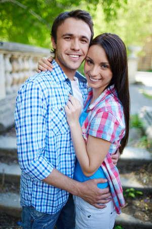 parejas enamoradas: Pareja feliz abrazando y mirando a la cámara al aire libre Foto de archivo