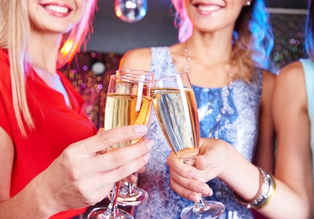 clubber: Happy friends clinking with flutes of champagne