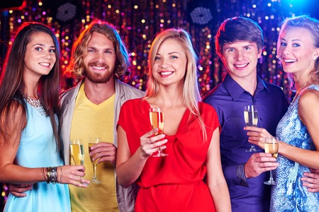 liquor girl: Happy friends with flutes of champagne looking at camera at party Stock Photo