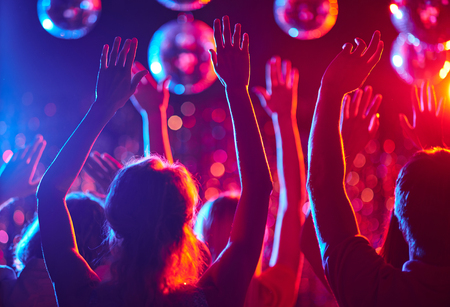 nacht: Menge von Menschen mit erhobenen Armen tanzen in Nachtclub