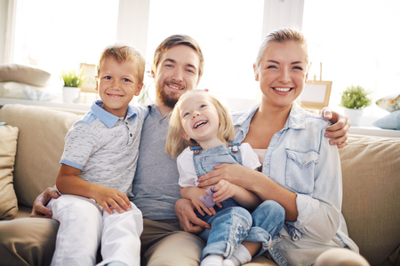 Happy family sitting on sofa at home and looking at camera Stock Photo
