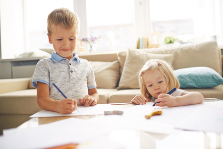 girls youth: Adorable siblings drawing together at home