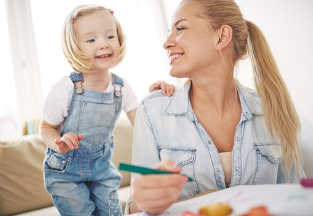 childcare: Curious girl touching her mother shoulder Stock Photo