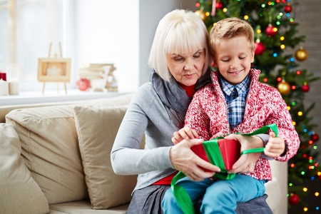 unpack: Mature woman helping her grandson untie gift-box on Christmas eve