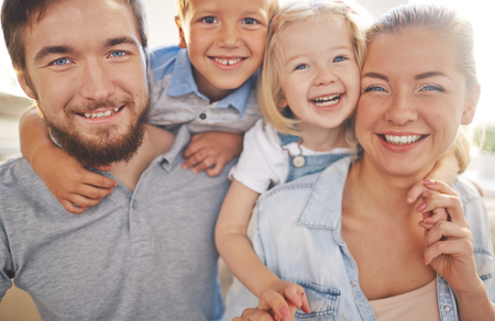 young boy smiling: Happy family of parents and two children looking at camera