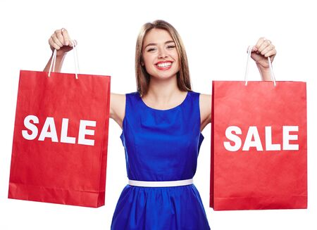 paperbags: Cheerful shopaholic with toothy smile holding two paperbags announcing sale Stock Photo