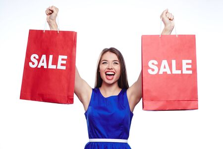 ecstatic: Ecstatic shopaholic holding two paperbags in raised hands Stock Photo