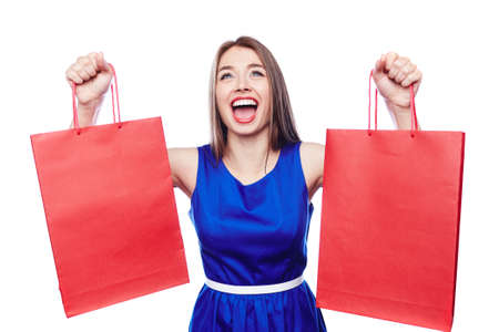 Ecstatic shopaholic with red paperbags in raised hands expressing triumph Stock Photo
