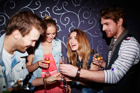 flutes: Cheerful friends with flutes of champagne spending time in nightclub