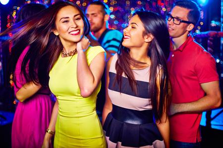 gente che balla: Due ragazze felici ballare in discoteca su sfondo dei loro amici