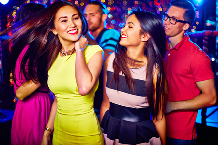 nightclub: Two happy girls dancing in nightclub on background of their friends Stock Photo