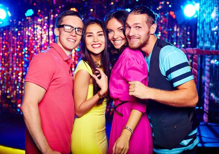 adult entertainment: Friendly clubbers looking at camera at party