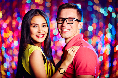 Cheerful young couple looking at camera in nightclub Stock Photo