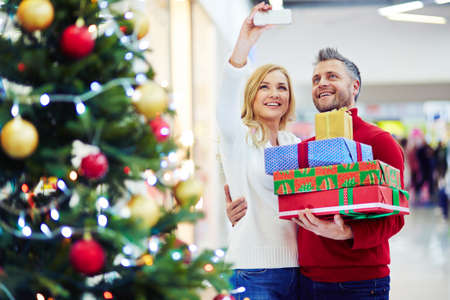 happy christmas: Couple taking selfie with gif boxes in the mall