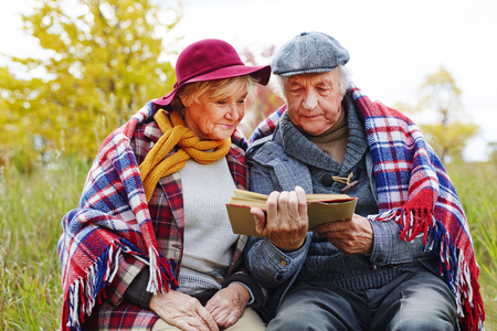 headcloth: Concentrated senior couple reading interesting book outdoors