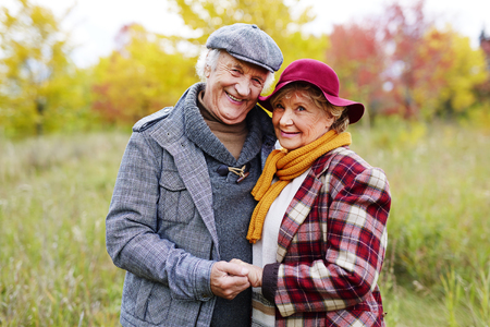 headcloth: Positive loving senior couple posing for camera