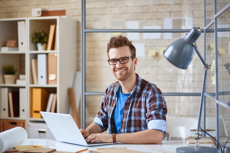 designer: Portrait of a positive guy working with laptop Stock Photo