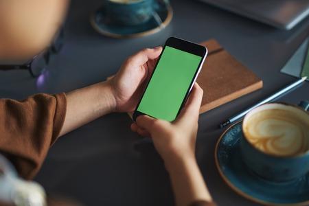 držení: Osoba, která používá smartphone, když odpočívá v kavárně