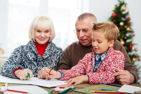 letter writing: Boy writing a letter to Santa with his grandparents Stock Photo