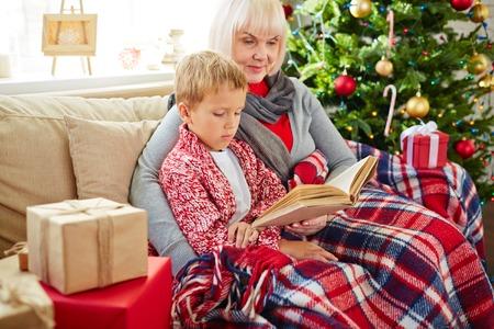 La abuela de leer historia de la Navidad a su nieto Foto de archivo