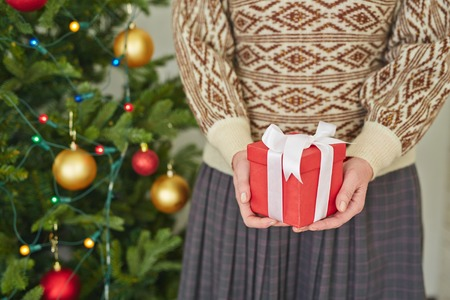 giftwrap: Woman holding a gift box in hands