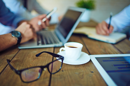 coffee meeting: Cup of coffee and eyeglasses in working environment Stock Photo