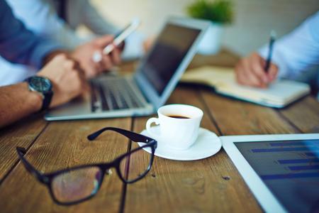 hombre tomando cafe: Taza de café y gafas en el entorno de trabajo Foto de archivo