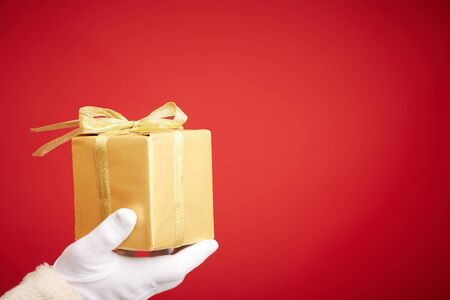 gloved: Gloved Santa hand holding giftbox wrapped into golden paper Stock Photo