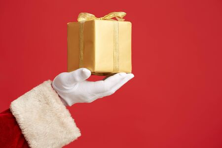 giftbox: Gloved Santa hand with golden giftbox