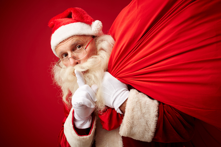 silence: Santa with sack of xmas gifts asking for silence Stock Photo